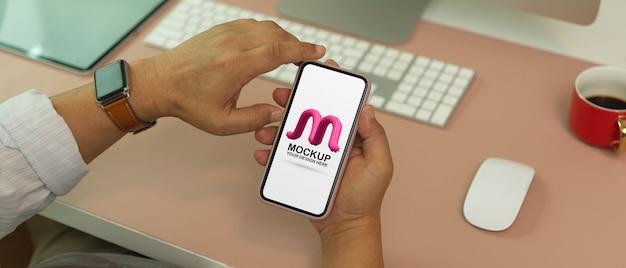 Foto recortada de homem segurando maquete de smartphone na mesa de escritório moderno