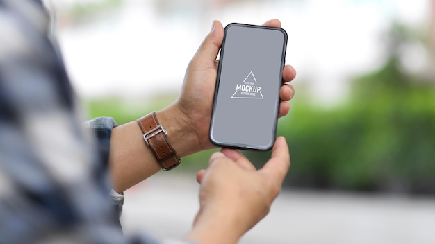 Foto recortada de mãos masculinas segurando uma maquete de smartphone