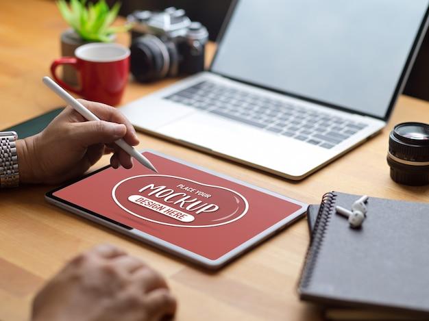Foto recortada de masculino desenhando um mock up tablet com caneta na mesa de madeira com material de escritório