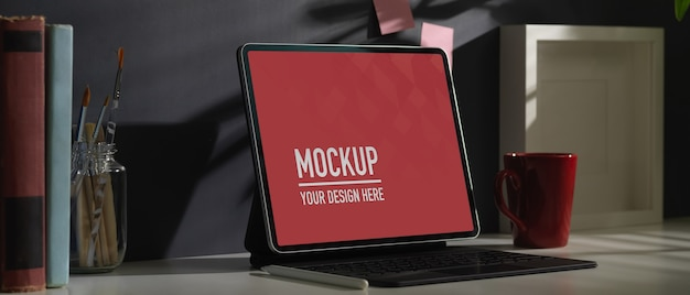 Foto recortada de mesa de trabalho com maquete de tablet, caneca de café e decorações