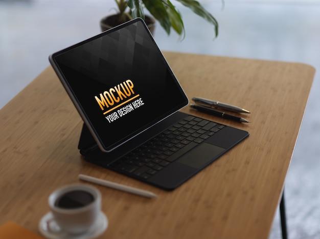 Foto recortada de simulação de tablet digital com teclado, xícara de café e canetas na mesa de madeira