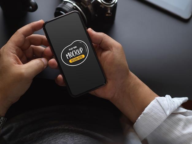 Foto recortada de trabalhador masculino usando simulação de smartphone enquanto trabalhava na mesa preta