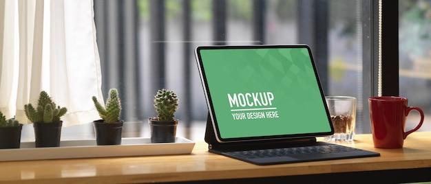Foto recortada de um espaço de trabalho portátil com simulação de tablet em um bar de madeira em um café
