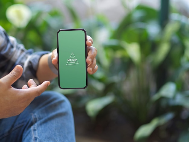 Foto recortada de um homem mostrando a maquete da tela do smartphone