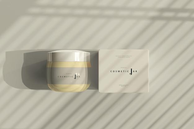 Frasco cosmético e maquete da caixa nas sombras
