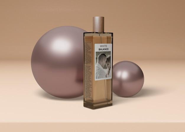 Frasco de perfume ao lado de bolas