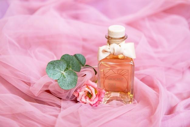 Frasco de perfume com flores na superfície rosa têxtil