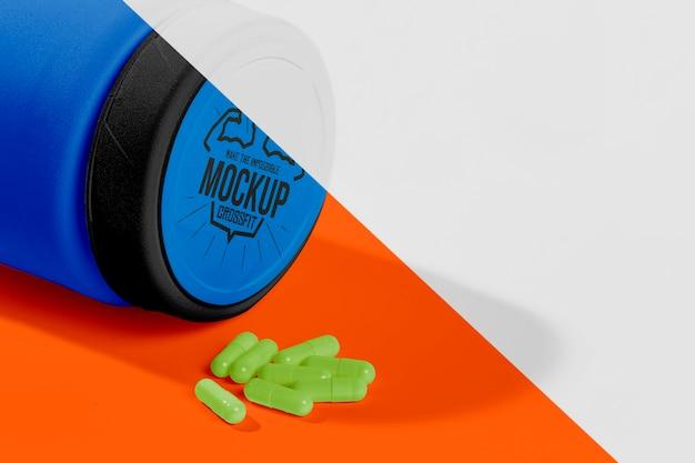 Frasco de proteína azul e maquete de comprimidos verdes