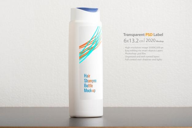 Frasco de shampoo para cabelo na frente de um fundo cinza claro