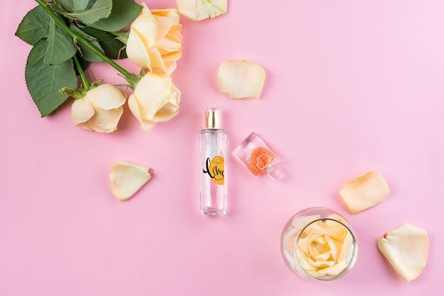 Frascos de perfume com flores no fundo rosa