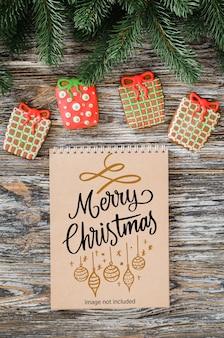 Fundo de natal com maquete de caderno marrom, biscoitos de gengibre e pinheiro