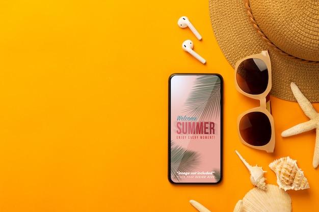 Fundo de verão com modelo de maquete de telefone e acessórios de praia em fundo laranja vibrante