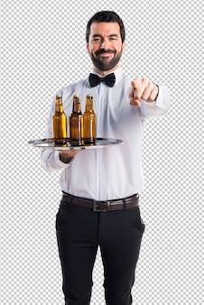Garçom com garrafas de cerveja na bandeja apontando para a frente
