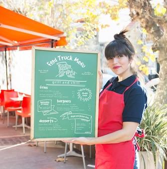 Garçonete apresentando placa com menu