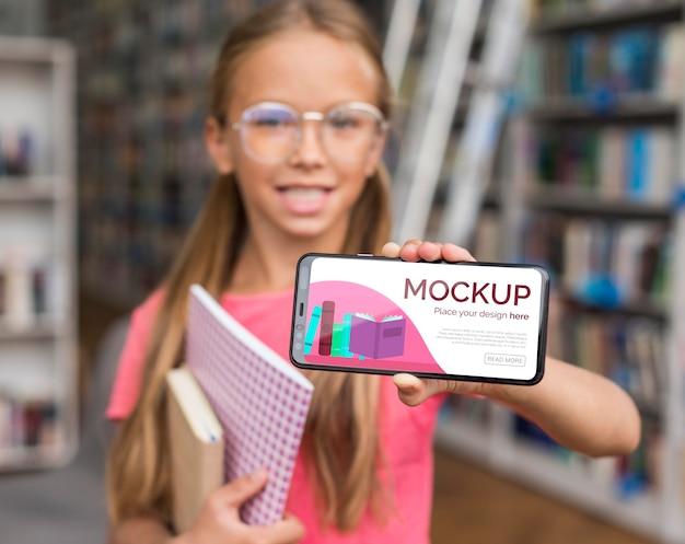 Garota de meio de tiro na biblioteca mostrando modelo de telefone