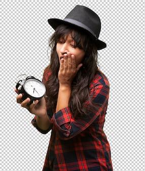 Garota latina segurando um despertador