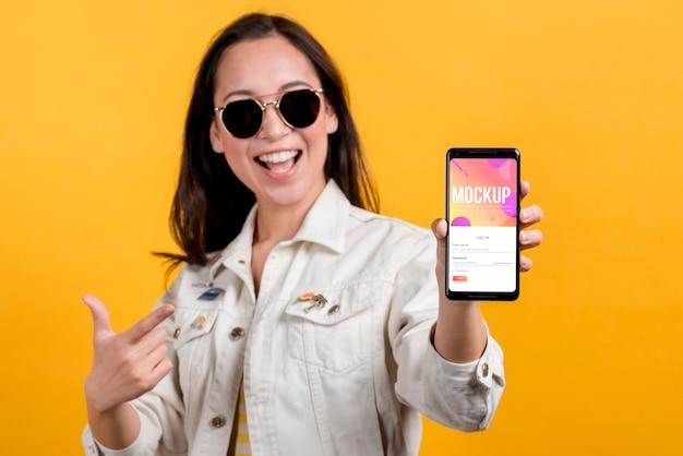 Garota legal de tiro médio segurando um smartphone