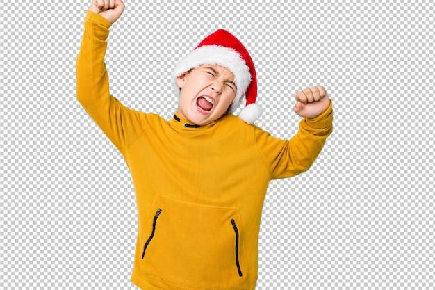 Garotinho, comemorando o dia de natal, usando um chapéu de papai noel, comemorando um dia especial, saltos e levante os braços com energia.
