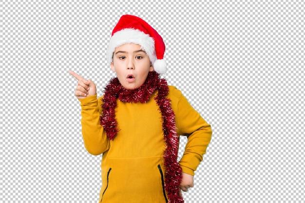 Garotinho, comemorando o dia de natal, usando um chapéu de papai noel isolado apontando para o lado