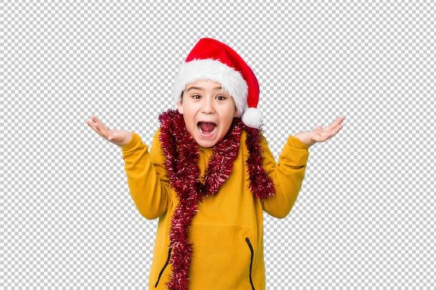 Garotinho comemorando o dia de natal usando um chapéu de papai noel isolado comemorando uma vitória ou sucesso, ele fica surpreso e chocado.