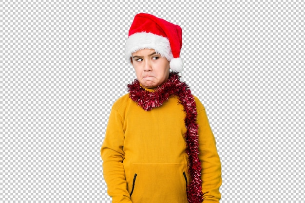 Garotinho comemorando o dia de natal usando um chapéu de papai noel isolado confuso, sente-se duvidoso e inseguro.
