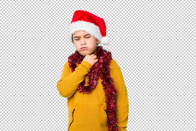 Garotinho comemorando o dia de natal usando um chapéu de papai noel isolado sofre dor na garganta devido a um vírus ou infecção.