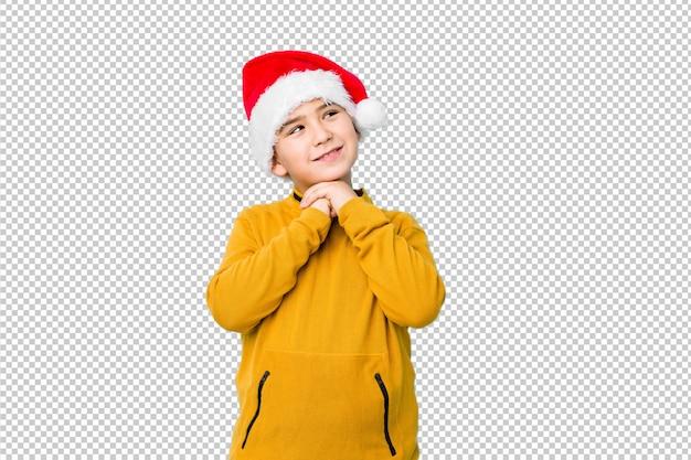 Garotinho, comemorando o dia de natal, usando um chapéu de papai noel mantém as mãos sob o queixo, está olhando alegremente de lado.