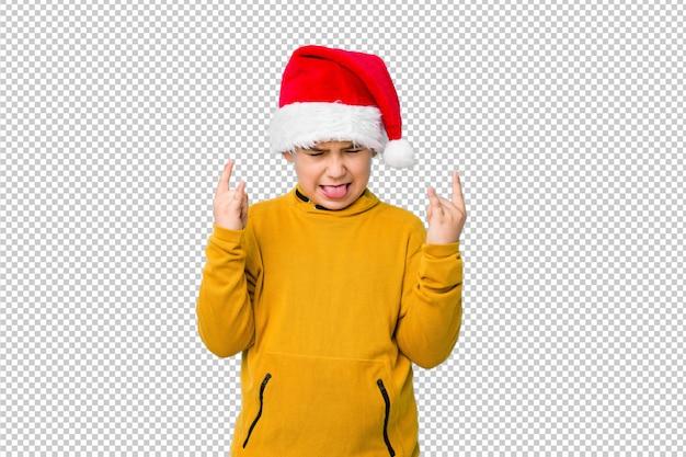 Garotinho, comemorando o dia de natal, usando um chapéu de papai noel, mostrando o gesto de pedra com os dedos