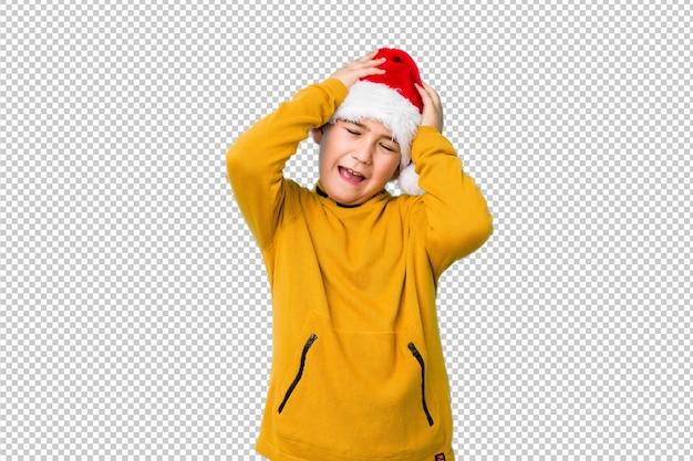Garotinho, comemorando o dia de natal, usando um chapéu de papai noel ri alegremente, mantendo as mãos na cabeça. conceito de felicidade.