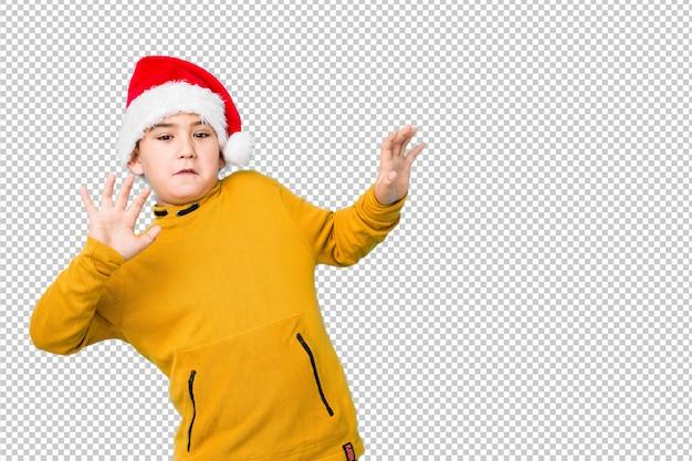 Garotinho comemorando o dia de natal usando um chapéu de papai noel sendo chocado devido a um perigo iminente