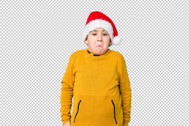 Garotinho, comemorando o dia de natal, vestindo um chapéu de papai noel encolhe os ombros e abre os olhos confusos.