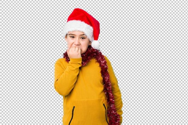 Garotinho, comemorando o dia de natal, vestindo um chapéu de papai noel isolado unhas cortantes, nervoso e muito ansioso.