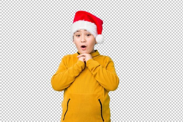 Garotinho, comemorando o dia de natal, vestindo um chapéu de papai noel, rezando para dar sorte, boca espantada e abertura, olhando para a frente.