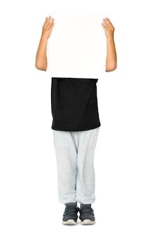 Garotinho, segurando a placa de papel vazio em branco, retrato de estúdio de rosto coberto