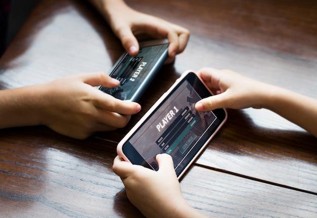 Garoto jogando um jogo para celular contra sua irmã