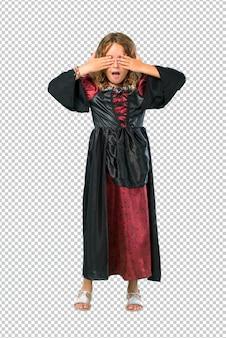 Garoto vestido como um vampiro em feriados de halloween cobrindo os olhos pelas mãos