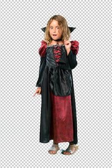 Garoto vestido como um vampiro em feriados de halloween em pé e pensando uma idéia