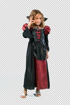 Garoto vestido como um vampiro em feriados de halloween, mostrando um sinal de ok com os dedos