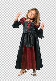 Garoto vestido como um vampiro em feriados de halloween sorrindo e mostrando sinal de vitória