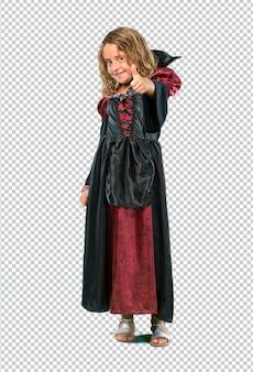 Garoto vestido como um vampiro no feriado de halloween dando um polegar para cima gesto e sorrindo