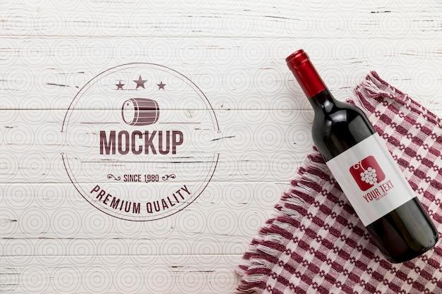 Garrafa de vinho tinto de vista frontal e toalha de cozinha