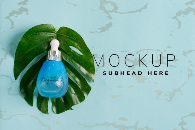 Garrafas azuis com óleo essencial natural de cosméticos ou loção sobre um fundo azul pastel com folhas verdes tropicais.