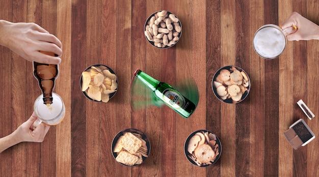 Girando a garrafa de cerveja na maquete de mesa de madeira