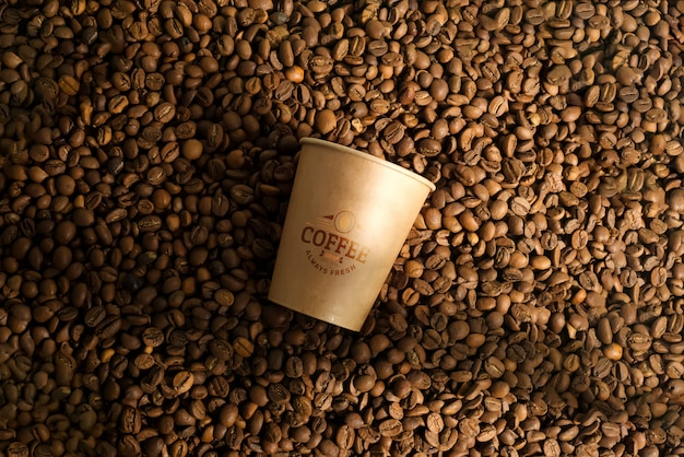 Grãos de café aromáticos e copo de maquete de papel.