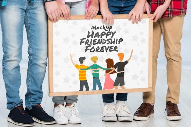 Grupo de crianças segurando cartaz mock-up juntos
