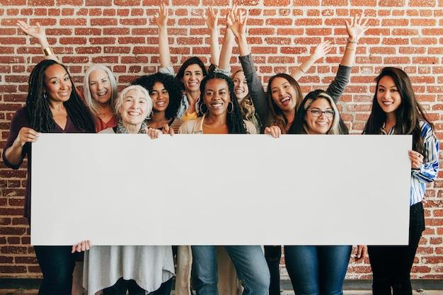 Grupo de diversas mulheres mostrando uma maquete de banner em branco
