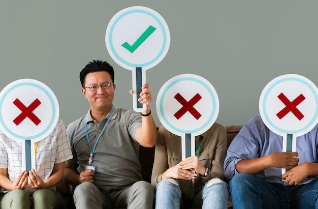 Grupo de pessoas segurando ícones verdadeiros e falsos