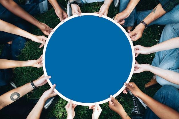 Grupo de pessoas segurando uma placa azul redonda