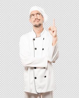 Hesitante jovem chef apontando para cima com o dedo