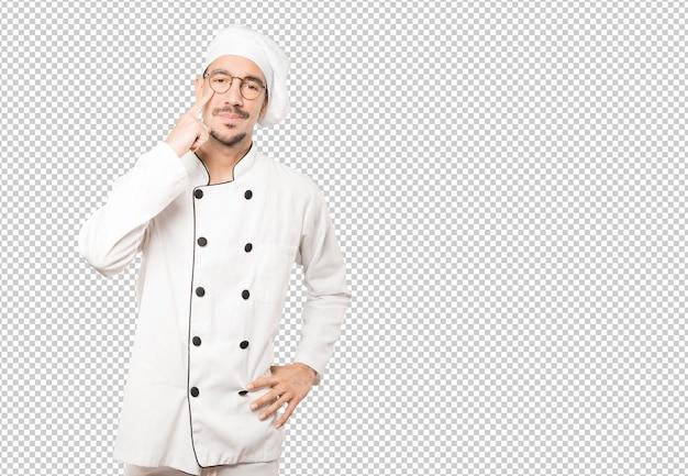 Hesitante jovem chef fazendo um gesto de cuidado com a mão apontando para o olho